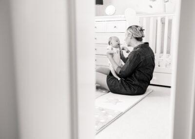 looking through door at new mum sat on floor in nursery holding baby