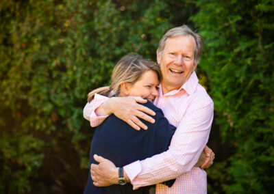adult daughter and elderly father hugging in garden
