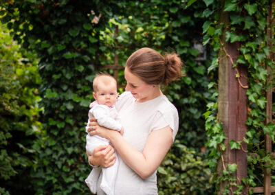 mum holding baby in the garden smiling