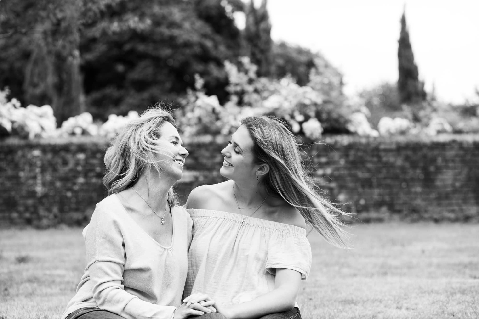 mother and teenage daughter sat in garden hugging