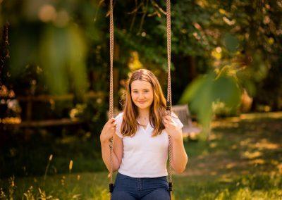 teenage girl sitting on swing in sunlight in garden in Amersham
