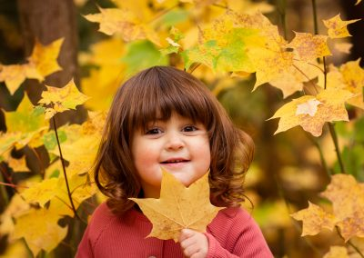 toddler girl holding a leaf smiling at camera in autumn woods in Wendover Bucks