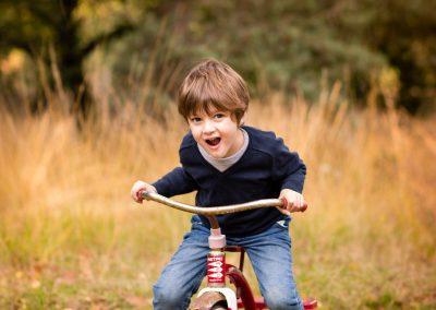 child on bike for outdoor family photoshoot in autumn